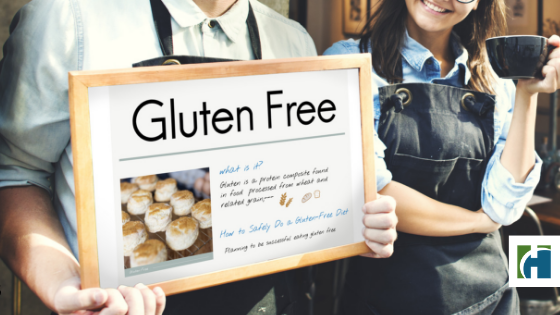 A man holds a gluten free sign with a smiling woman holding a cup of coffee in front of a restaurant.