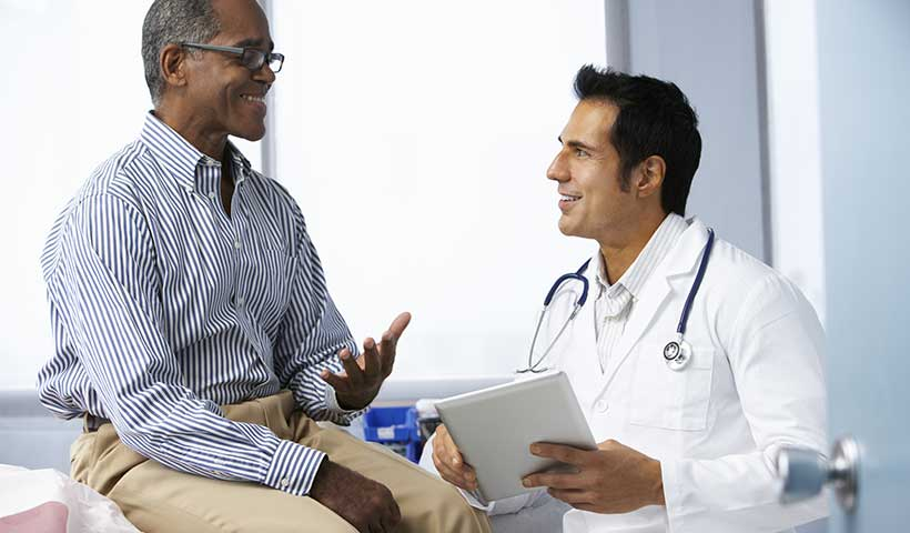 A male patient having a discussion with his male doctor in an exam room